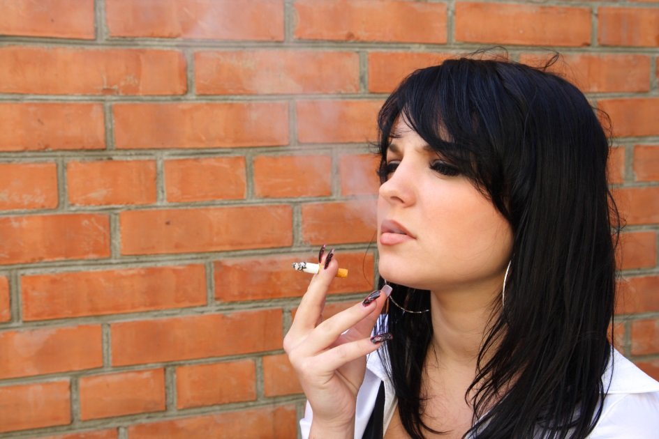 young woman smoking outside