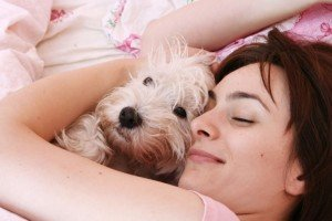 Woman curled up and sleeping with dog CanadianPharmacyMeds.com