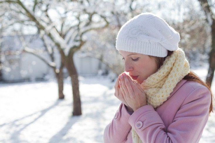 Woman breathing on hands while outside in winter CanadianPharmacyMeds.com